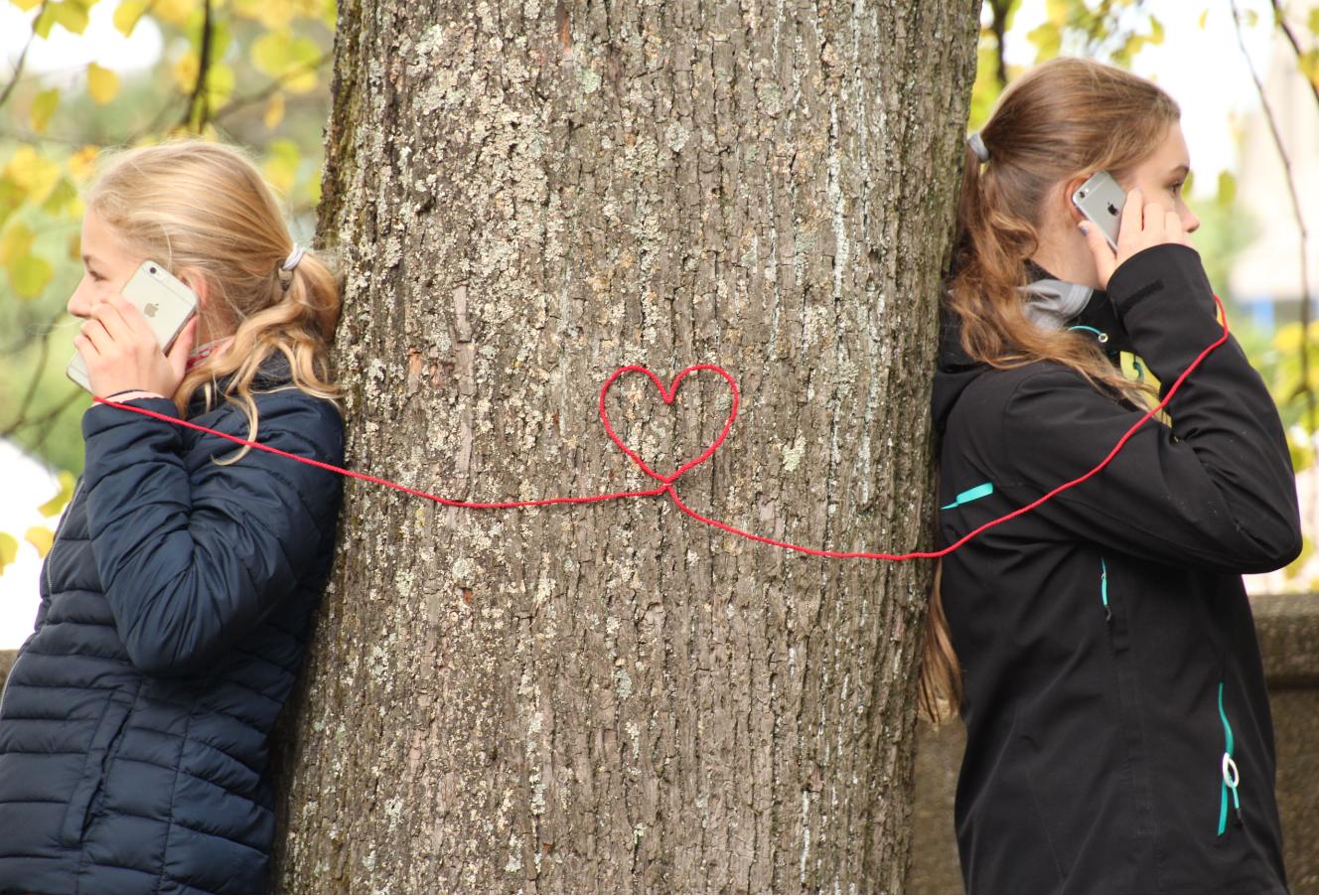 2 Mädchen telefonieren mit Abstand, rotes Band mit Herzchen verbindet die Handys