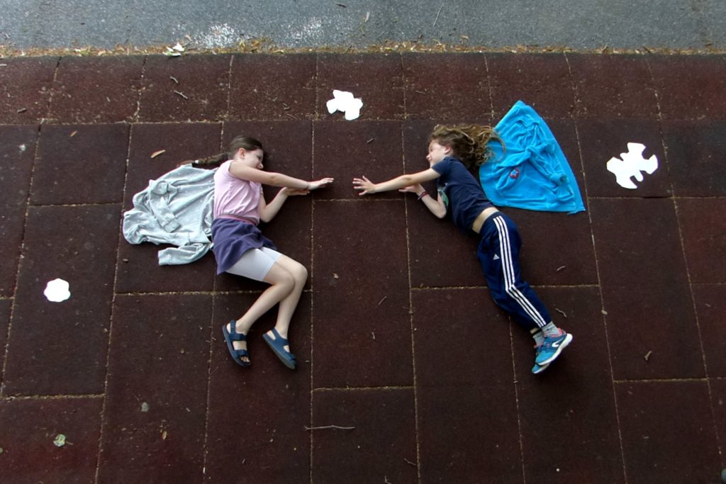 Zwei Mädchenauf dem Boden liegnd mit Flügeln, Arme zu einander streckend