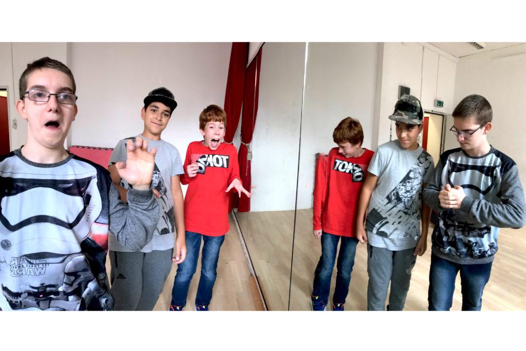 Drei Jungs gespiegelt im Spiegel mit Grimassen