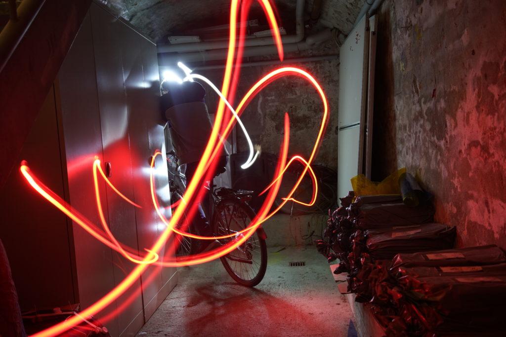 Dunkler Hintergrund mit Fahrrad und im Vordergrund rotgelbes Lightpainting