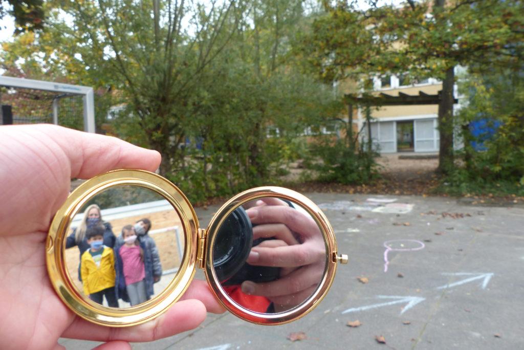 Handspiegel ausgeklappt, im Spiegel sind Kinder