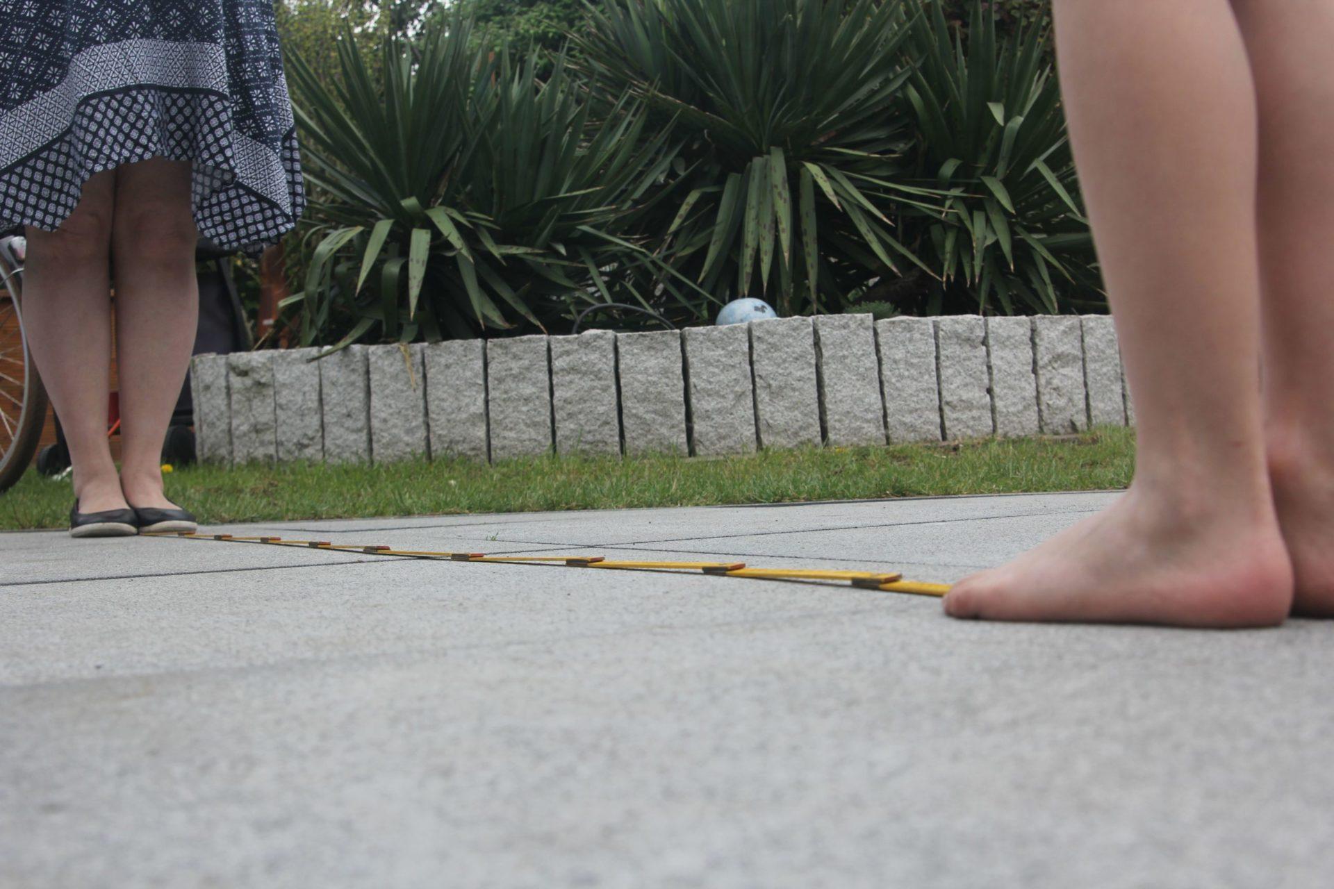 Zwei Kinder und ein Metermaß zwischen ihnen auf dem Boden