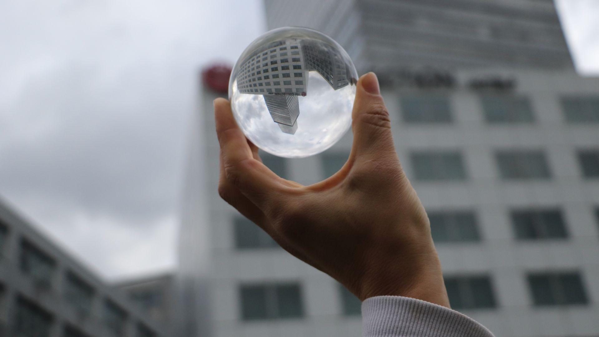 Eine Hand hält eine Glaskuel, darin spiegelt sich ein Gebäude