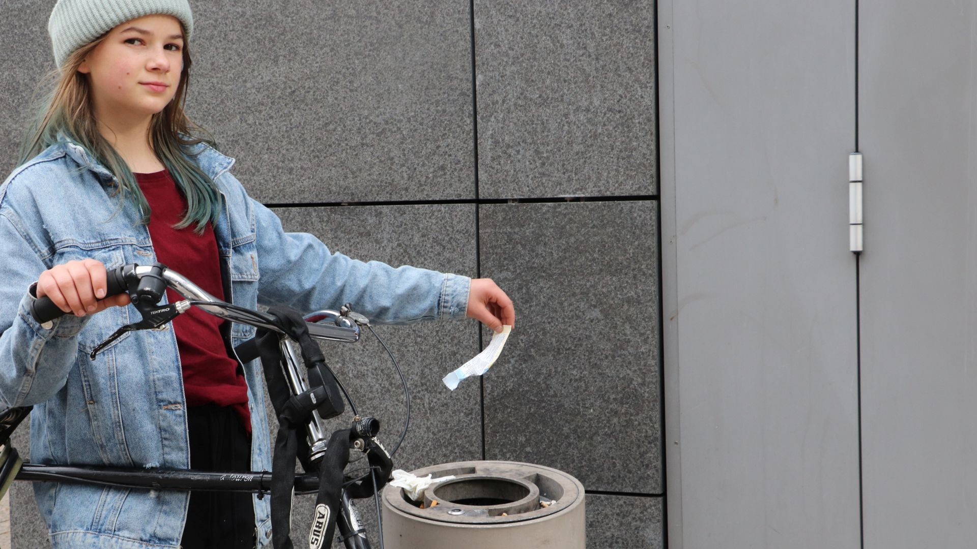 Mädchen lehnt an Fahrrad und wirft Müll in Mülleimer