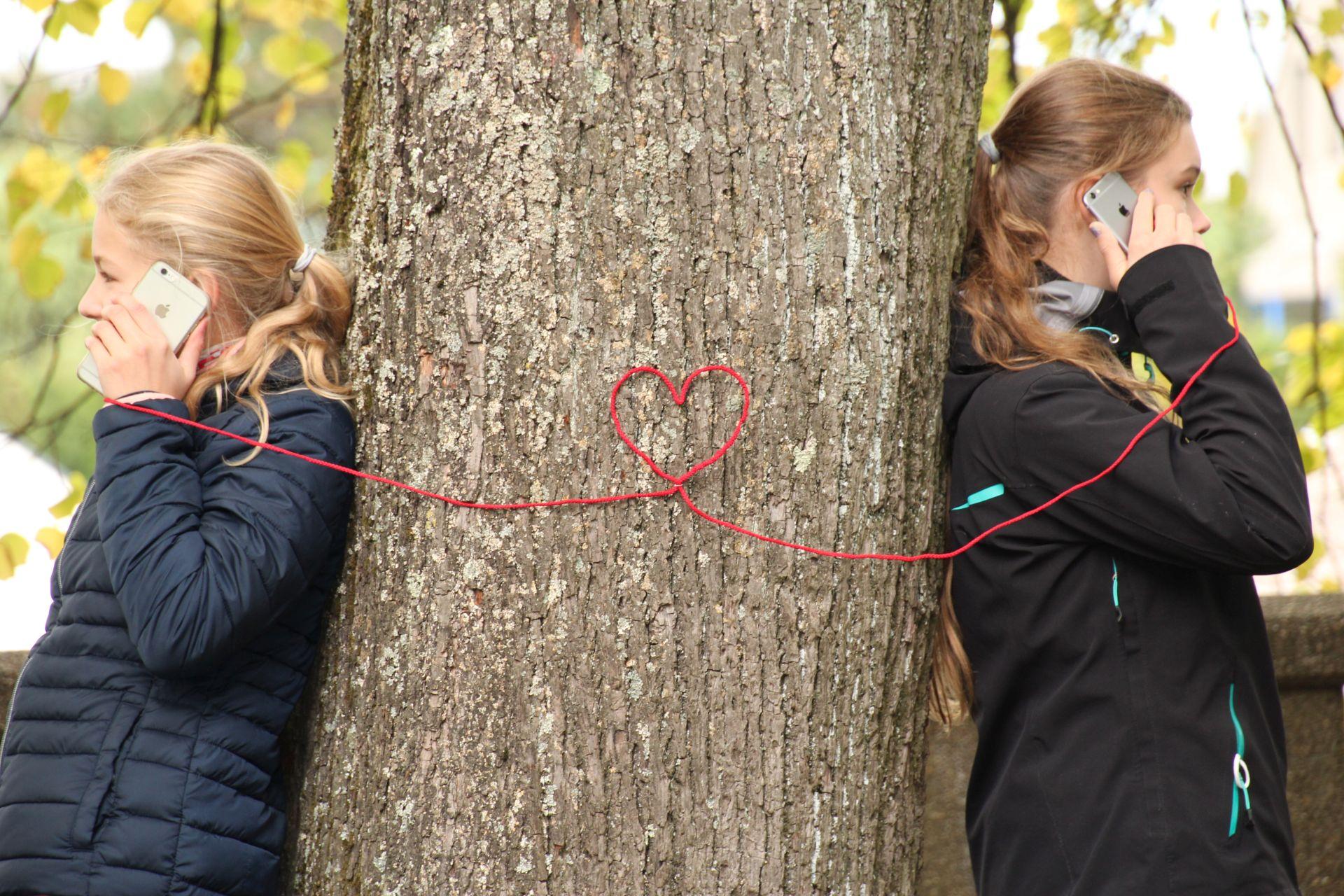 2 Mädchen telfonieren mit einem roten Kabel, welches ein Herz bildet, zwischen einem Baum