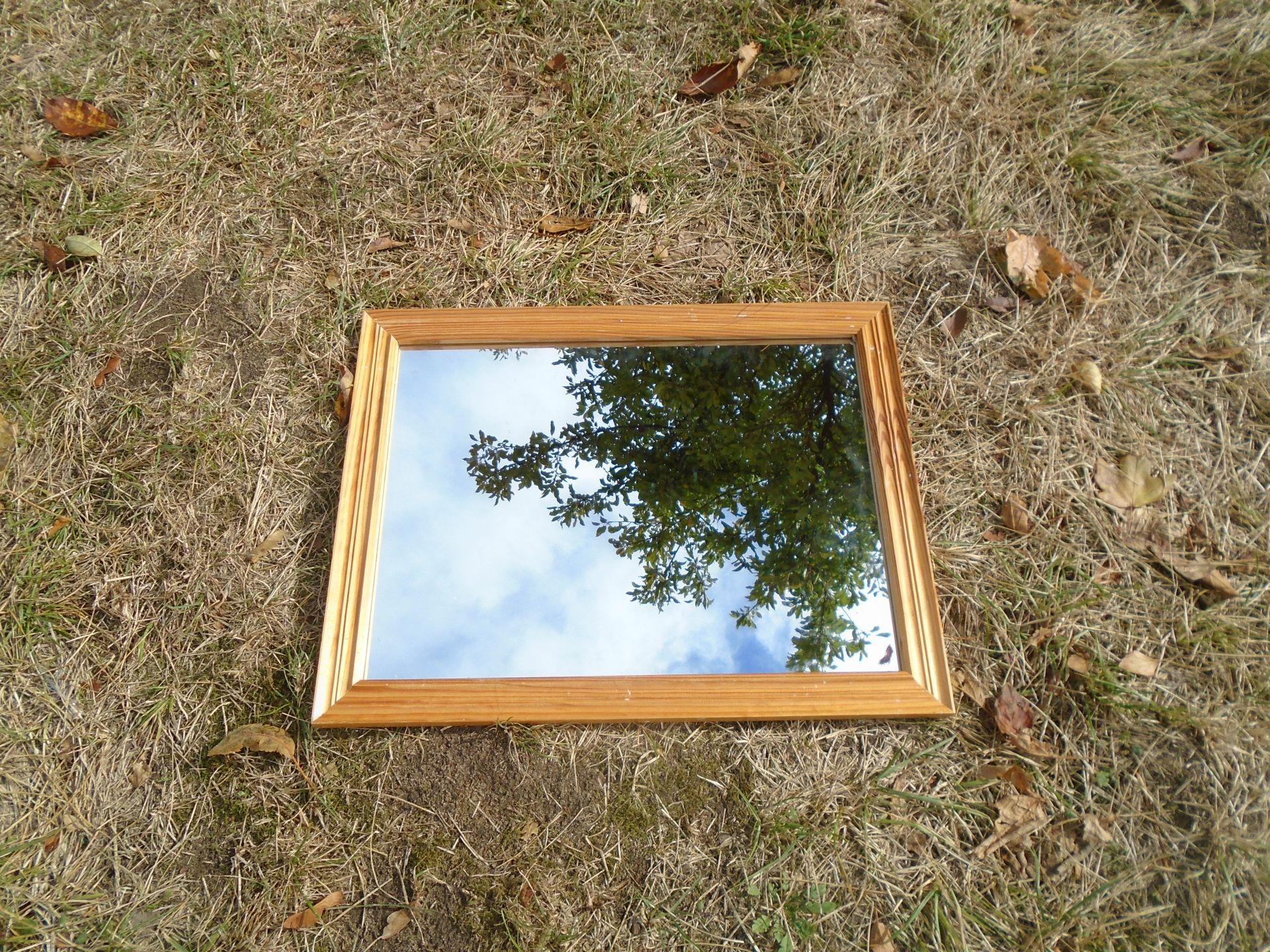 Ein Spiegel liegt auf Rasen und spiegelt den Himmel