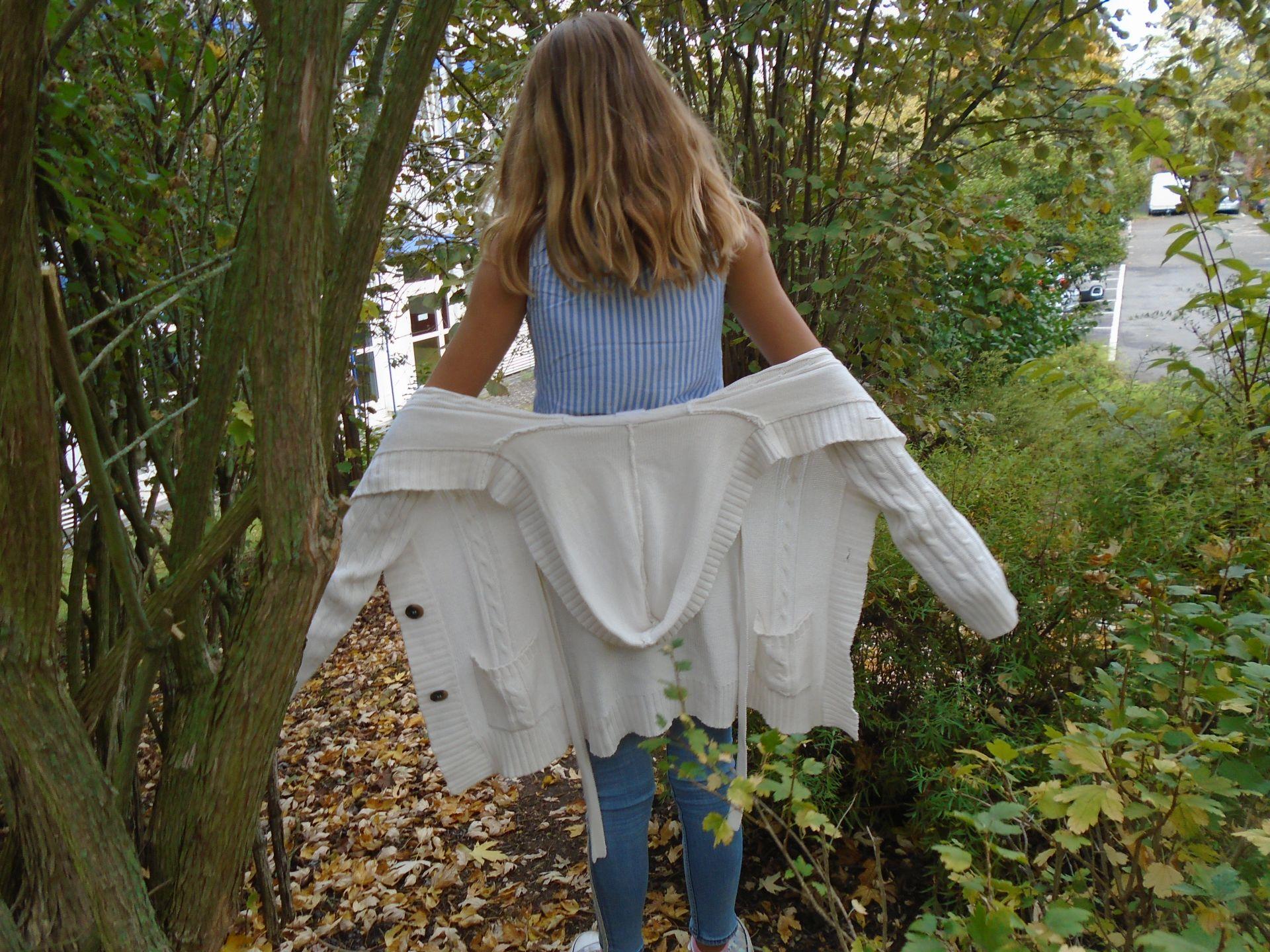 Mädchen im Wald mit Rücken zur Kamera und weiße Strickjacke hab ausgezogen