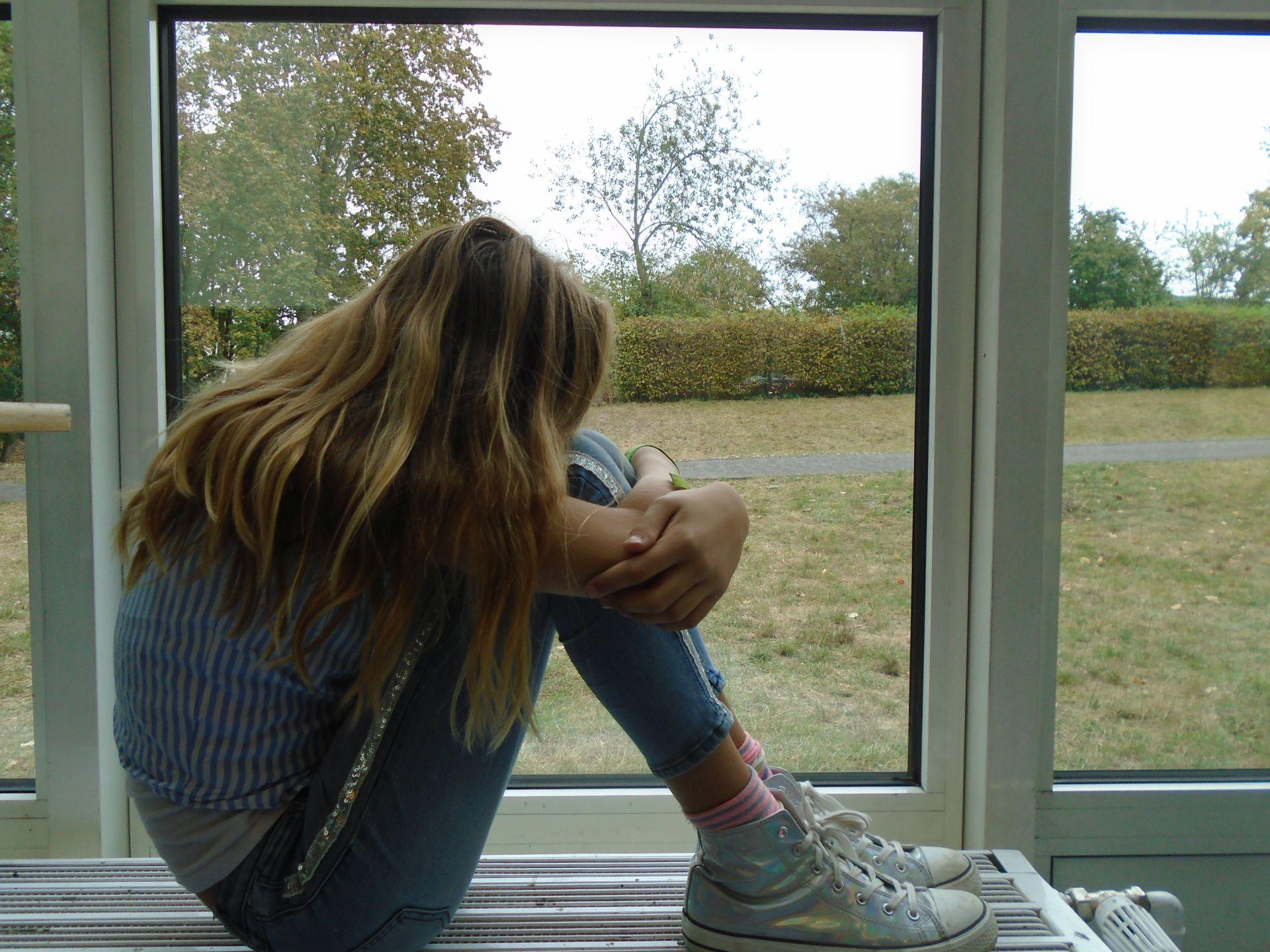 Mädchen sitzt mit angewinkelten beinen auf einer Heizung vor dem Fenster