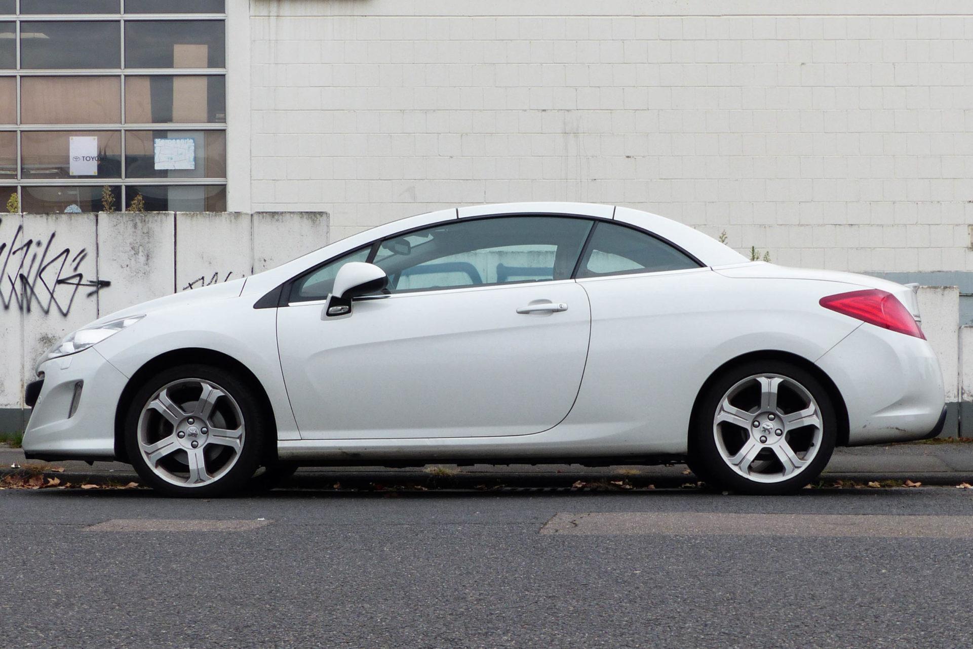 Weißes Auto steht vor weißer Wand