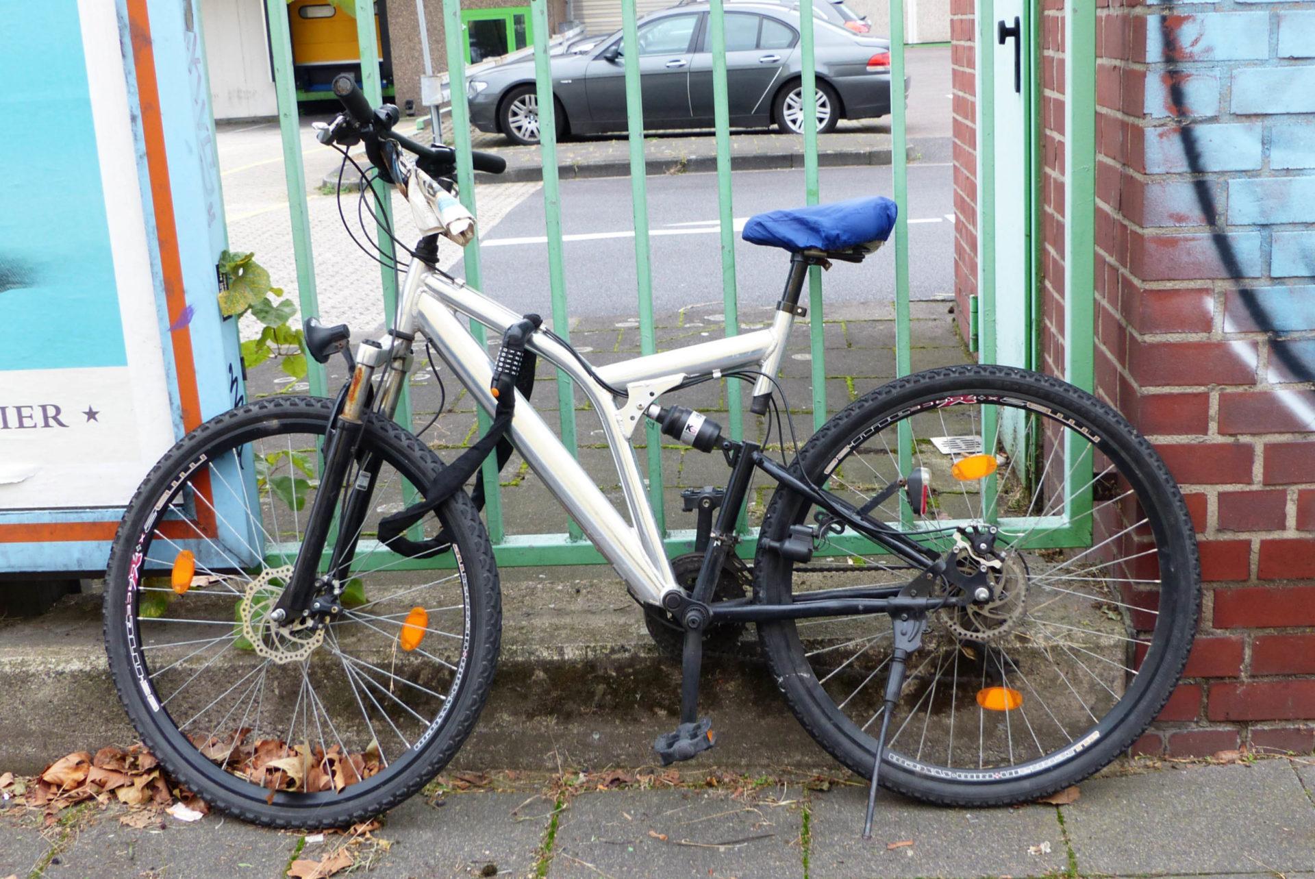 Fahrrad vor türkisen Zaun