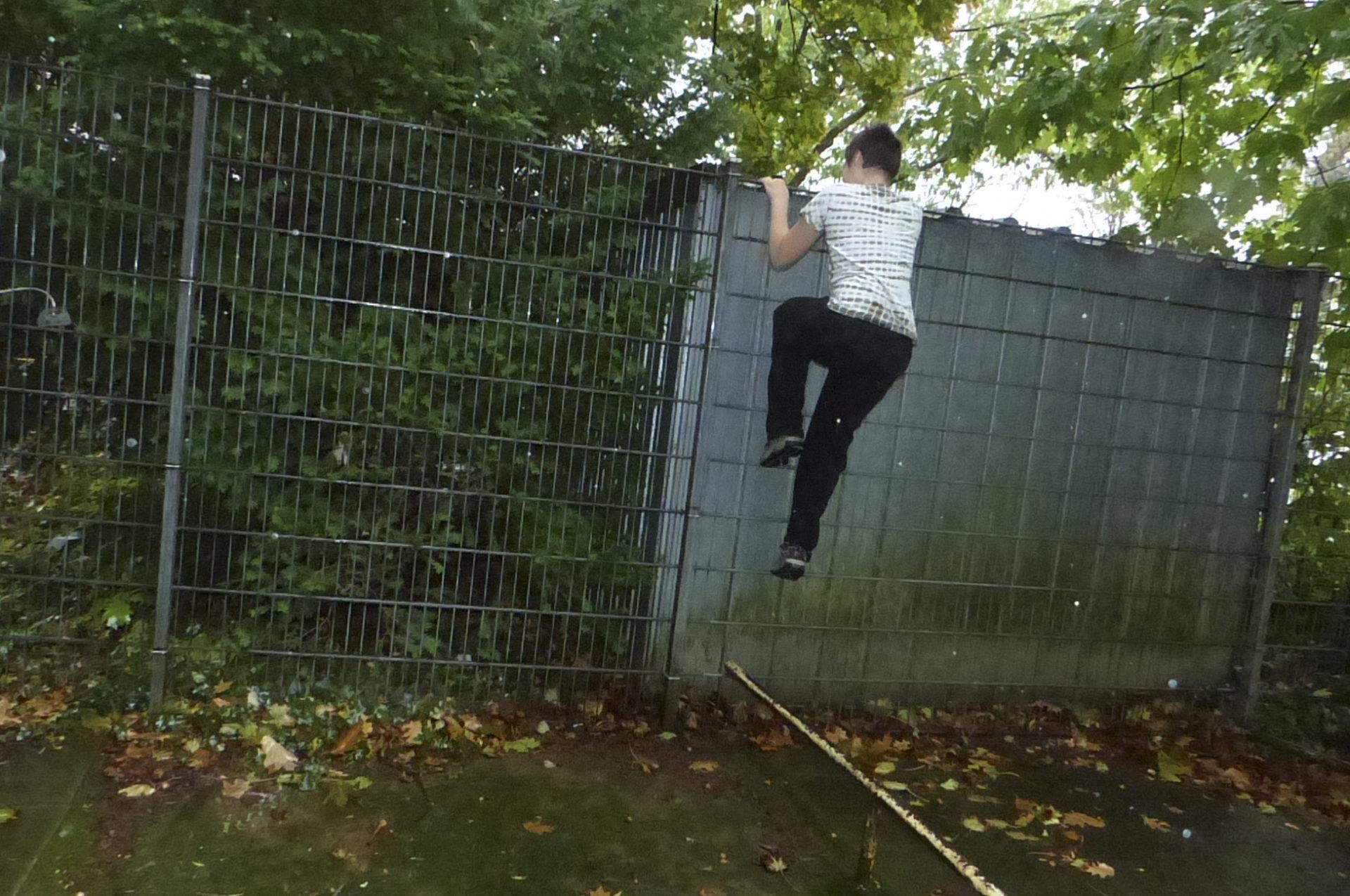 Kind klettert über Zaun