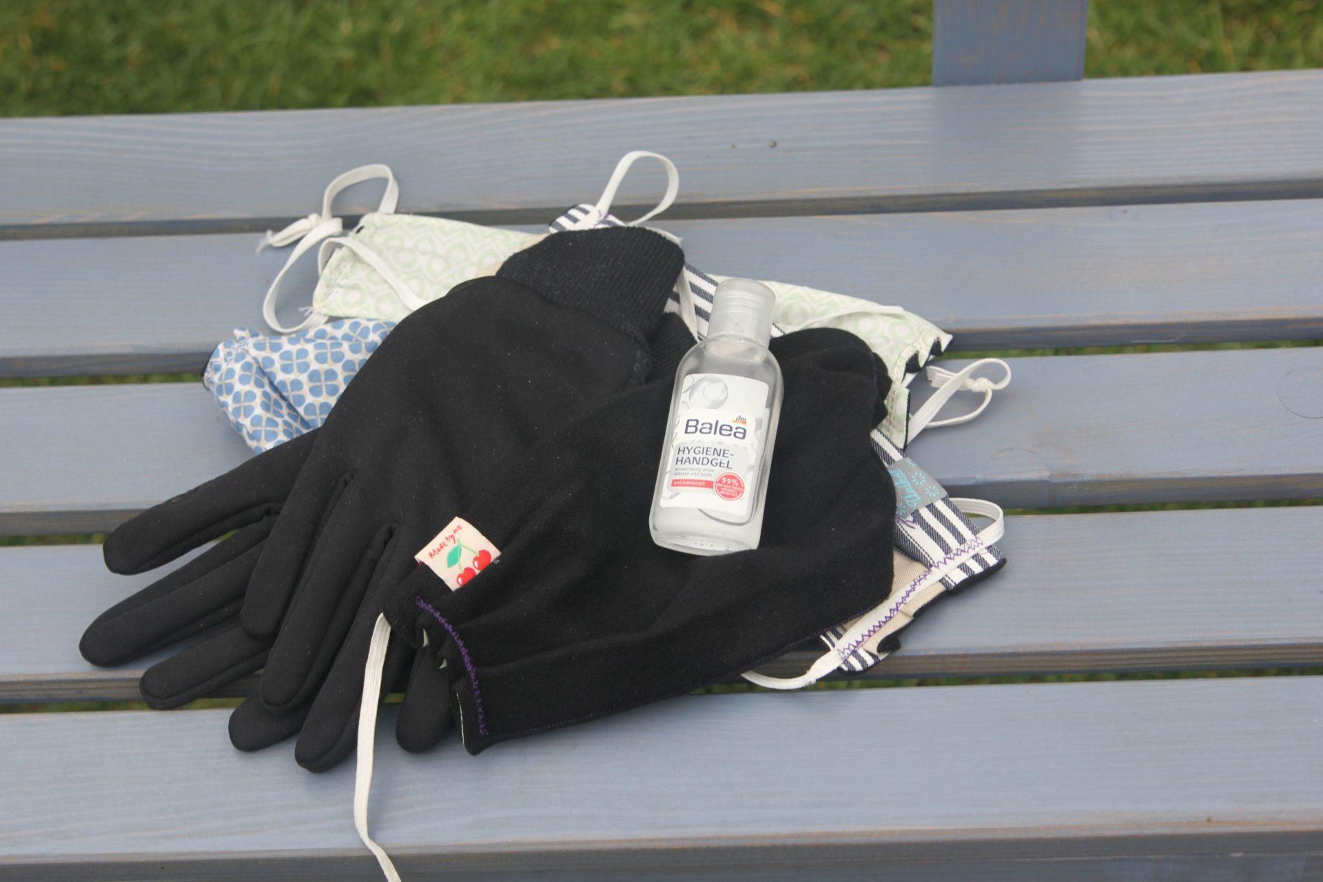 Handschuhe, Maske, Desinfektionsmittel liegen auf einer Bank