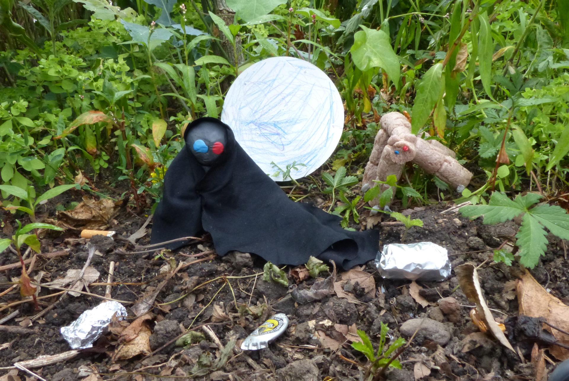Männchen aus Knete und Stoff im Gebüsch zwischen Müll