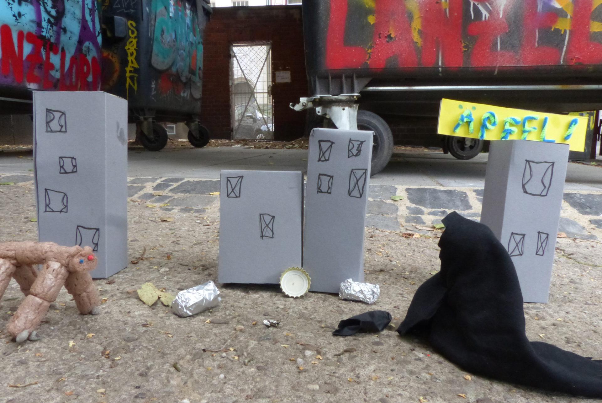 Männchen aus Knete und Stoff vor gebastelten Häusern mit Müll