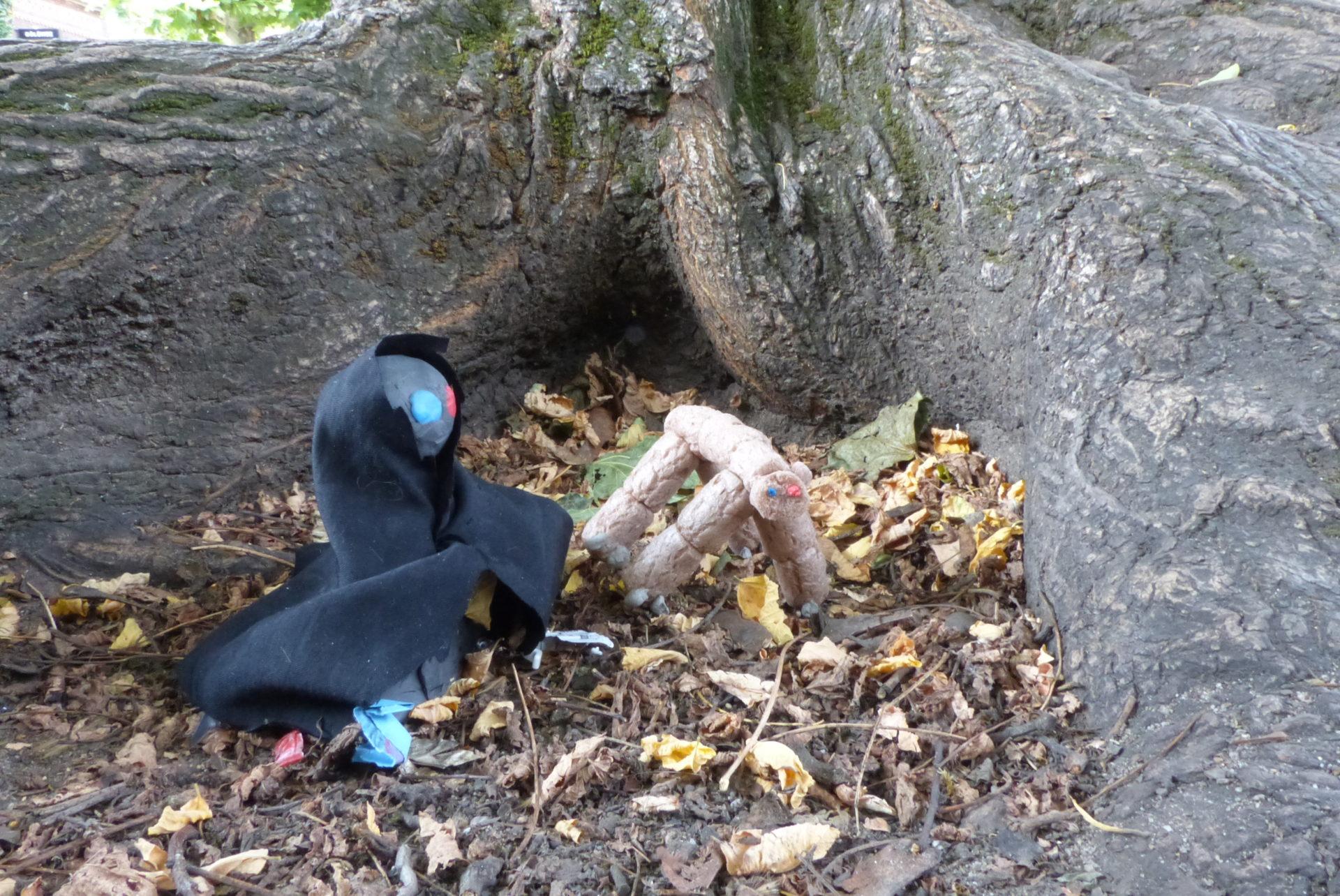 Männchen aus Knete und Stoff sitzen vor Baumstumpf