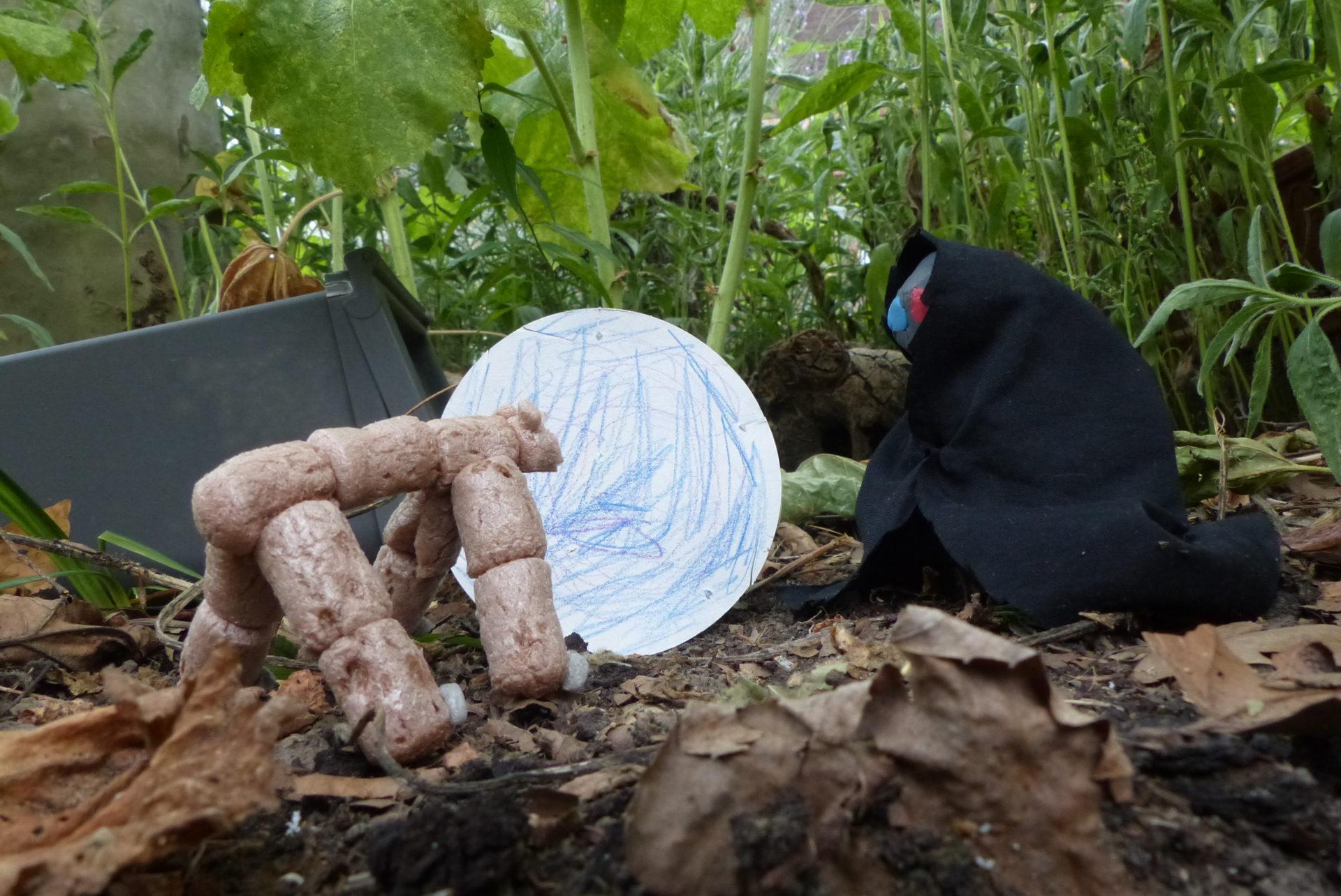 Männchen aus Knete und Stoff sitzend vor Müll im Gebüsch
