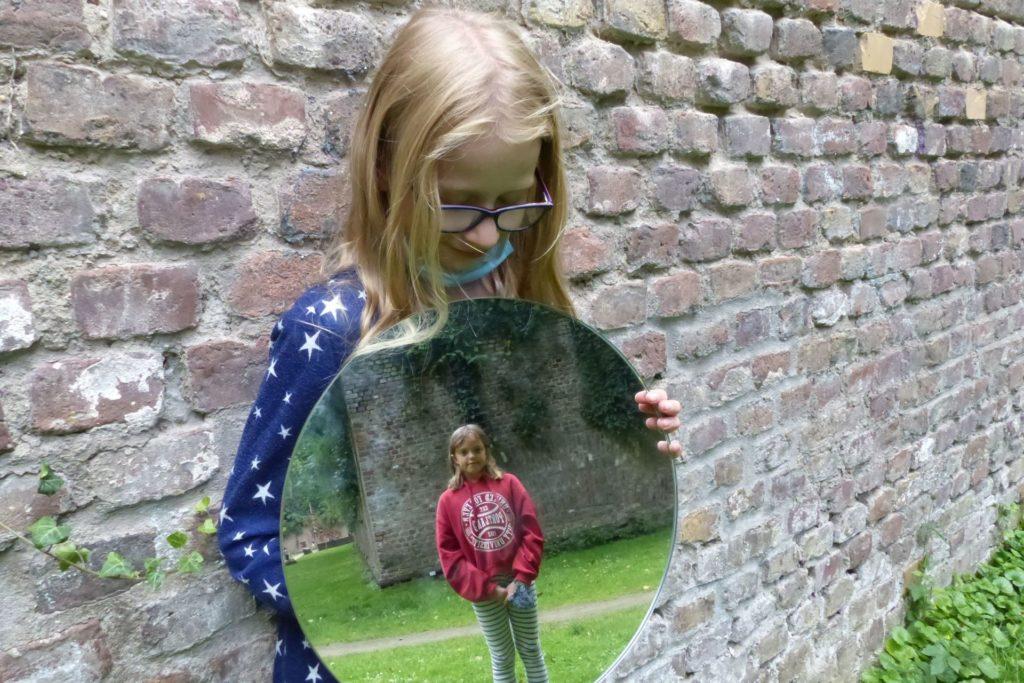 Mädchen vor einer Steinwand, mit Spiegel vor dem Bauch, darin spiegelt sich ein zweites Mädchen