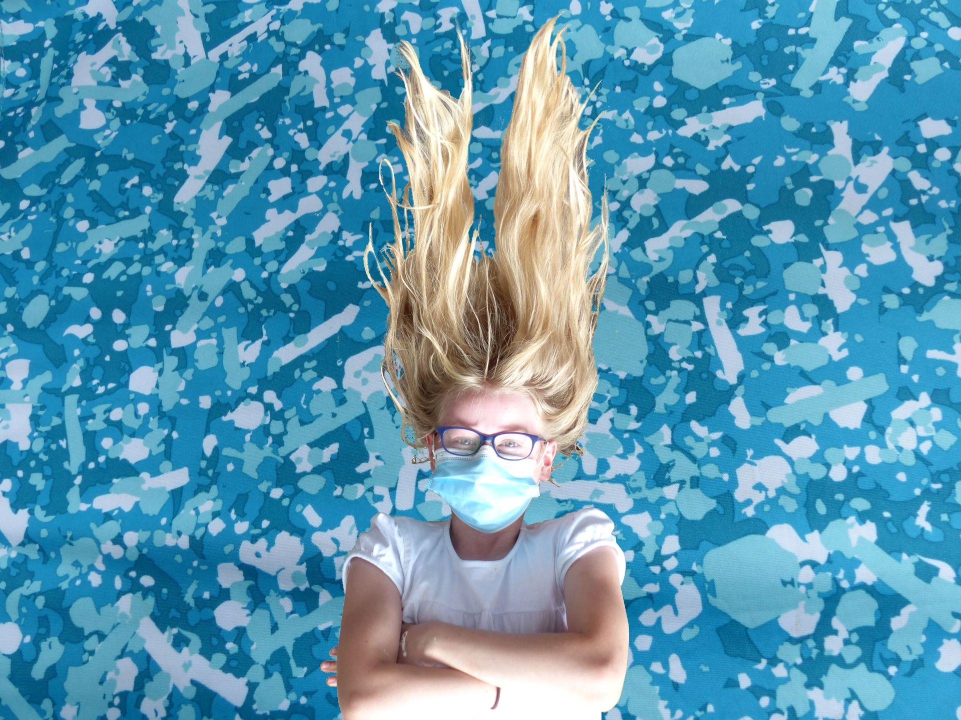 Mädchen mit MAske vor blauem Hintergrund, die Haare zu Bergen