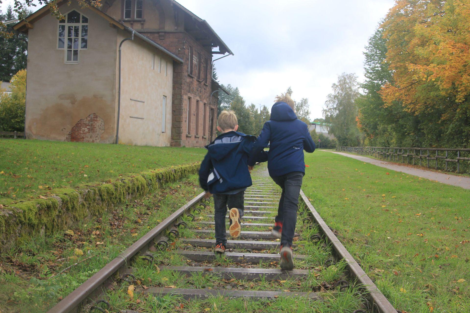 zwei Jungs rennen zwischen Bahnschienen