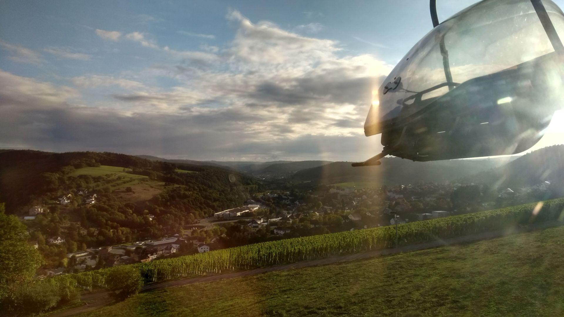 Tal mit grünem Gras, Häusern und blauem Himmel mit Schleierwolken