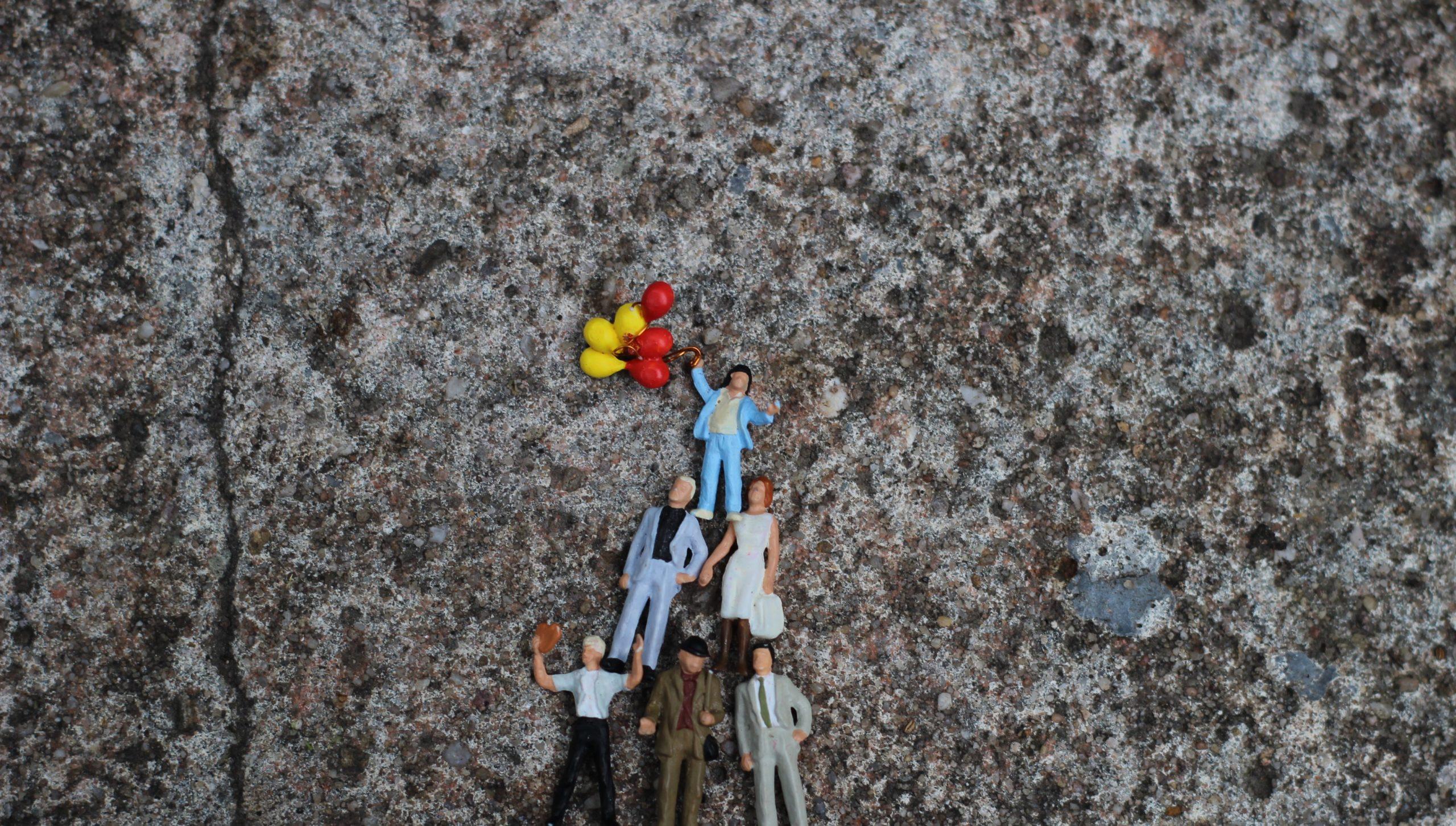 Kleine Figuren stehen in einer Pyramide zusammen